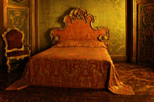 an old red and gold bed lays almost untouched