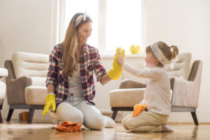 A woman and little girl high-five each other as they finish up cleaning the hardwood floor of their home for the spring season.