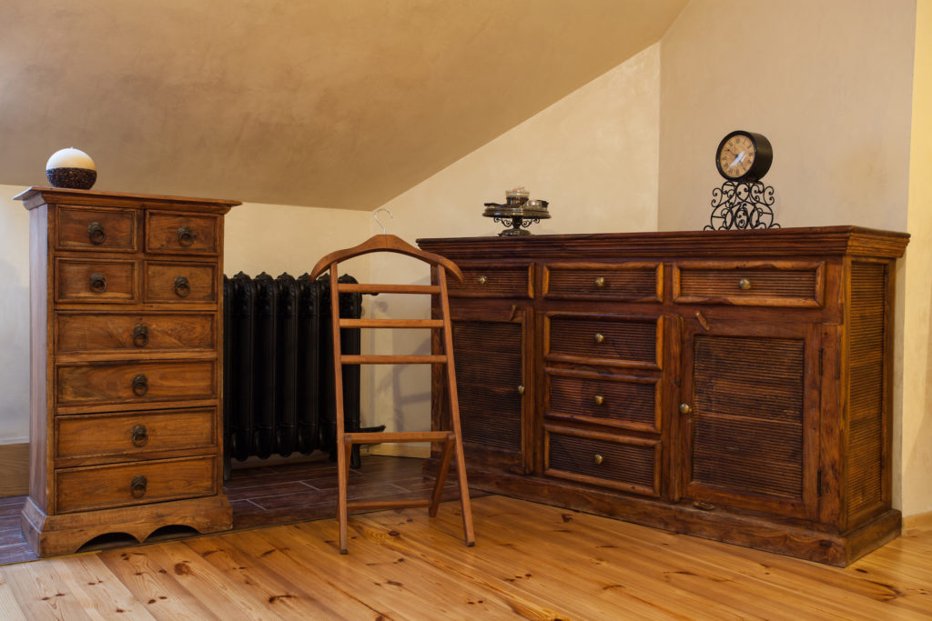 A bedroom with beautiful vintage furniture including an armoire and a dresser